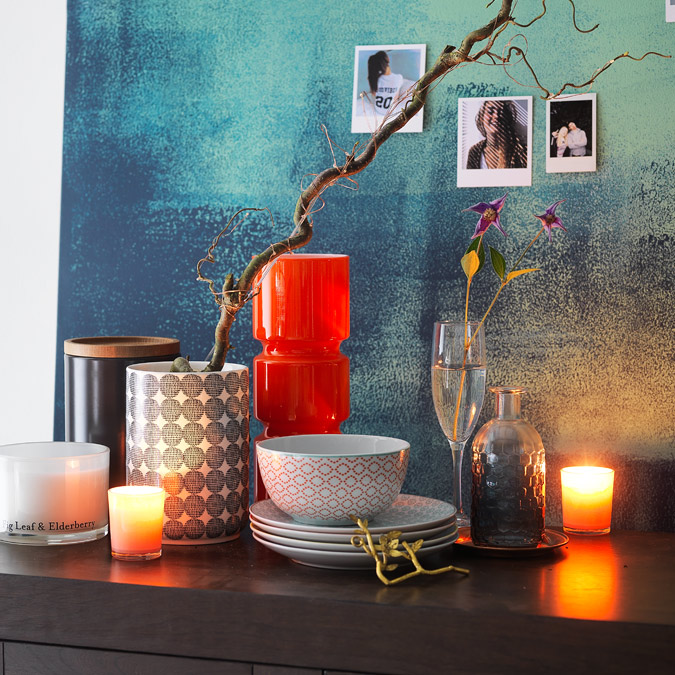 Vase, canister and fairy lights on sideboard.
