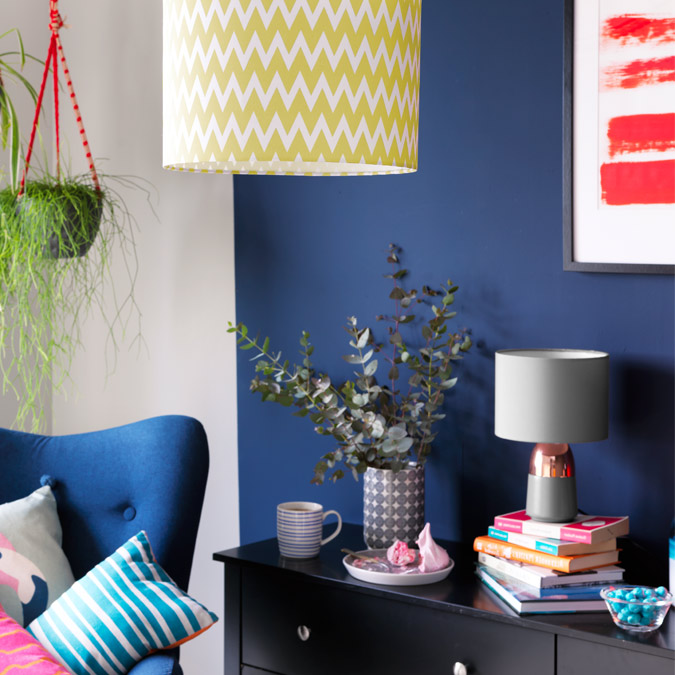Yellow chevron pendant lamp shade in front of blue wall.