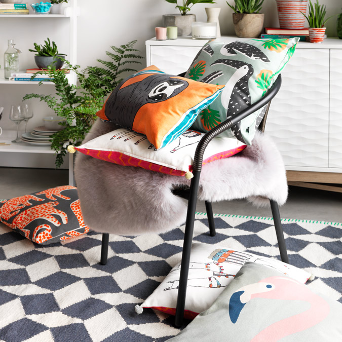 Metal chair with stacked cushions on geometric rug.
