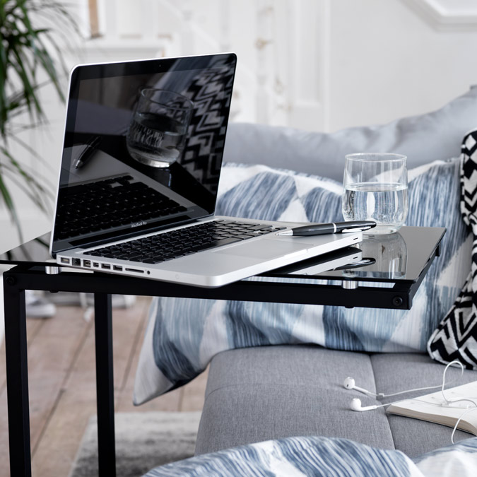 Black glass laptop tray with laptop over sofa bed.