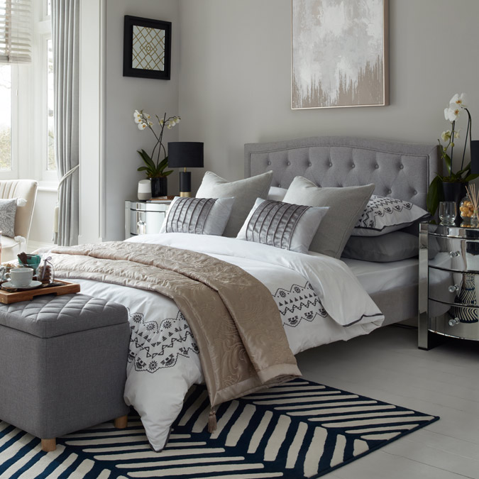 Luxury guest room with large grey double bed, embroidered bedding and mirrored bedside cabinet.