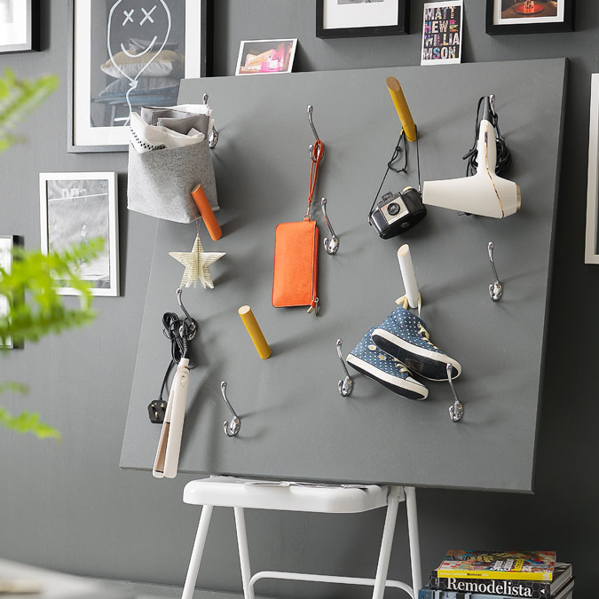 Grey painted board with coloured pegs for hanging up hairdryer and other items.