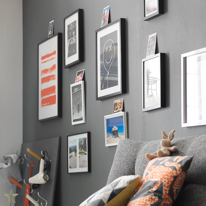 Grey painted wall with photo frames.