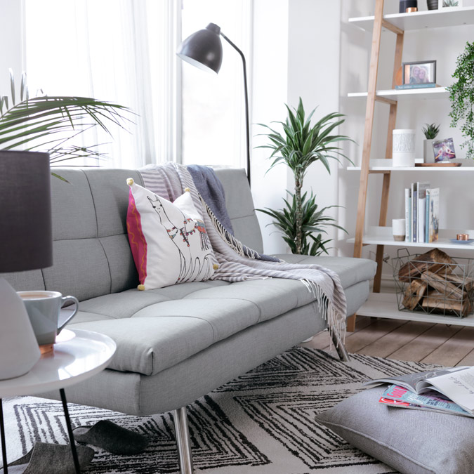 Grey sofa bed with cushion and throw on diamond pattern rug in living room.