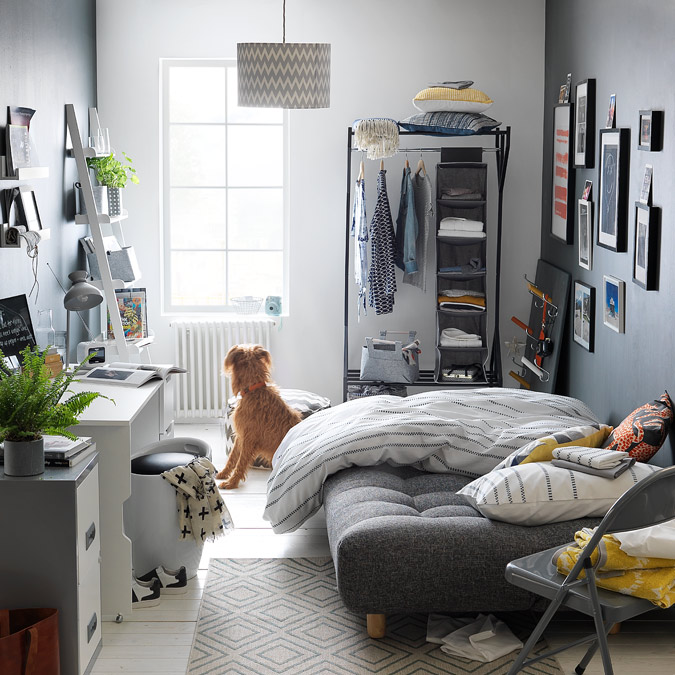 Grey spare room with double sofa bed, small hanging rail for clothes and desk space.